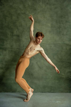 Ballet dancer poses at grunge wall, dancing studio Imagens