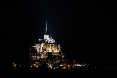 The famous Mont Saint Michel, in France, illuminated by its multiple floodlights photo