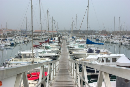 est: Ponton dans un port de Noirmoutier  Le temps est gris et souligne la linéarité des embarcations A jetty of a small harbor in Noirmoutier  Françe