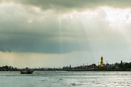 storm coming: The traditional big buddha beside the Chao Phraya River landscape with lighting from cloud before a storm coming.
