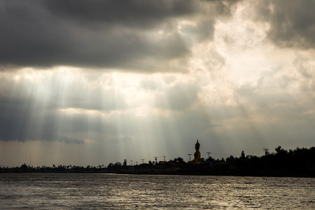 storm coming: The traditional big buddha beside the Chao Phraya River landscape silhouetted with lighting from cloud before a storm coming.