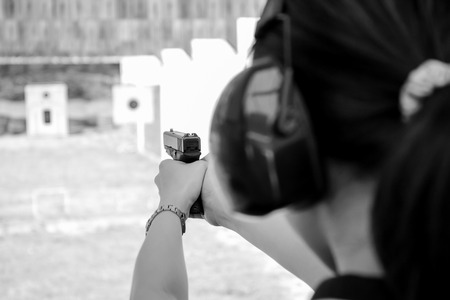 firearms: A women shooting a 9 m.m pistal in BW colour tone. Editorial