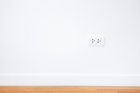 plug in: Modern female plug in white wall background.