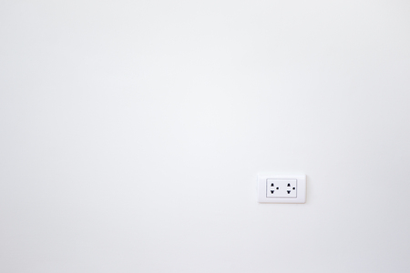 unplugging: Modern female plug in white wall background.