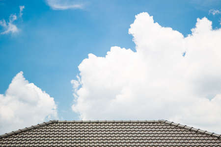Beautiful a group of clouds in the blue sky and roof top of modern home during the sun shin. Stock Photo