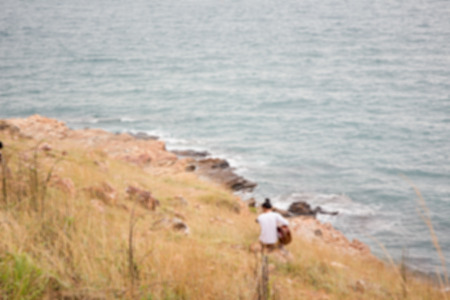 gutar: Blur image of a man who playing on the grass field on moutain near the sea. Stock Photo