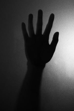 self harm: The photograpy of right hand against the window in horror concept close up.(Processed in black and white colour tone) Stock Photo