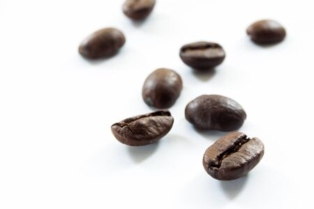 grained: Organic coffee beans in white background close up.