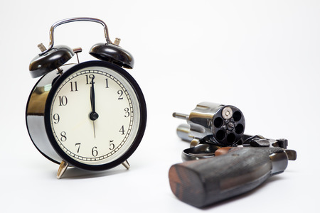 Classic alarm clock and  revolver handgun close up on white background.