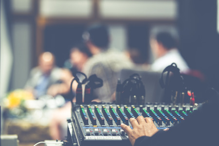 Sound engineer is controlling sound mixer board in concert event.(Processed in vintage colour tone) 免版税图像