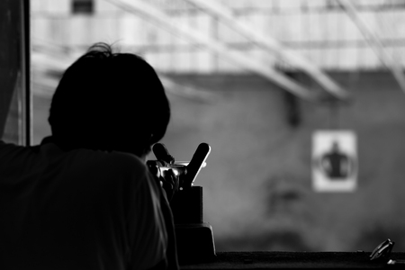 common target: Man shooting a rifle gun to human target processed in black and white colour tone.
