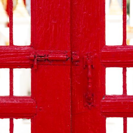 Old lockpad locked on a wooden red door with rusty chain close up background.