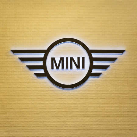 cooper: BANGKOK,THAILAND-DEC 3: Photograph of Mini Cooper's logo decorated on yellow wall close up.
