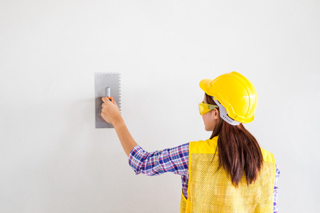 Women age between 25-30 years old wearing a yellow engineer hat plastering on wall. on wall.