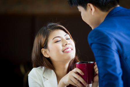 Asian couple aged between 25-30 years-old enjoy talking and drinking coffee together close up. Stock Photo