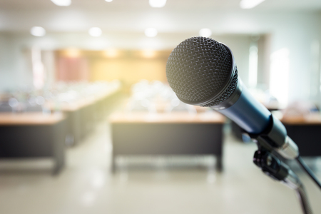 Wired microphone in front of the convention room without people. Stock Photo