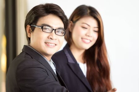 Asian business man aged between 30-35 years old grab his glasses with his female assistant behind.