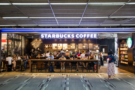 BANGKOK, THAILAND-APRIL 13: People in Starbucks coffee shop enjoying with their coffee and tapping on their smartphone on April 13, 2017 in Bangkok, Thailand.