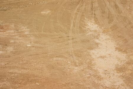 Photograph of red soil with heavy tire scratch on surface.