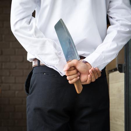 Mann versteckt Messer hinter in der Konzeptfotografie des Geschäfts. Standard-Bild