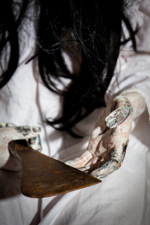 Women in white dress holding a knife on hands close up.  Concpet of horror and holloween. Standard-Bild