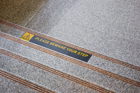 Please beware your step sticker on polished stone floor close up.