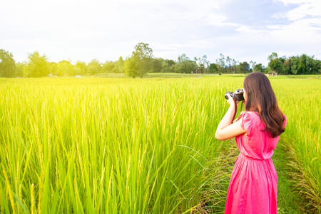 Pretty Asian girl in bright pink red enjoy landscape photographing with the vintage film camera.