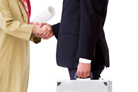 Arab business man shake hand with Asian business man in the blakc suit carrying a silver suit case. Banco de Imagens