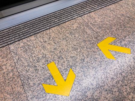 Yellow arrow sign on rail platform close up. Stock Photo