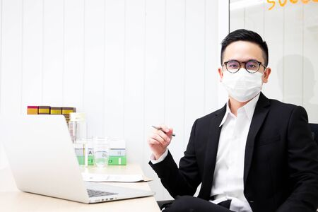 Portrait of Asian business man working in the office and masked a hygiene mask on his face