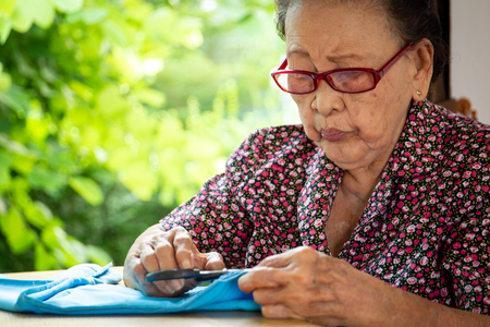 Elder Asian lady age between 80-85 years old sewing a cloth professionally.