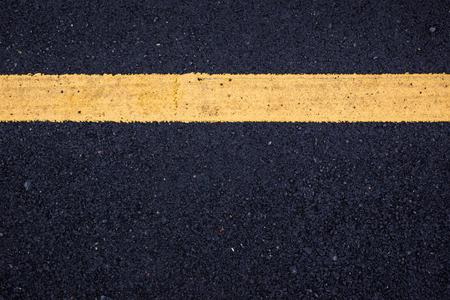 Żółta linia znak na czarnej asfaltowej drodze z bliska w tle.