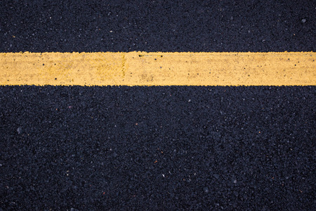 Yellow line sign on black asphalt road close up background.