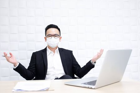 Asian business man working in the office and masking his face by a hygine mask.
