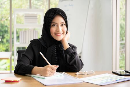 Portrait of smart beautiful Asian Muslim businesswoman working in the office, Diversity cultural and gender concept.