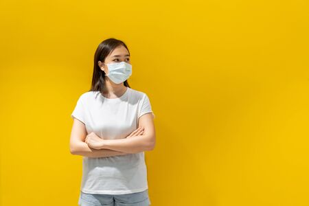 Asian young attractive woman wearing a protective hygiene mask over her face to protect flu and virus. Unwell influenza in infected woman portrait with yellow background. Covid19 and Coronavirus. 版權商用圖片