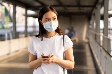 Beautiful young Asian woman wearing the protective mask while traveling in the city where fully with air pollution pm2.5. Unhealthy urban air pollution problem and coronavirus disease in Asia. Archivio Fotografico