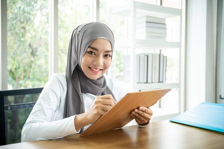 Asian muslim businesswoman writing on a clipboard. Multicultural and diverse ethnicity of people in workplace. Muslim secretary prepare a document for her boss. Modern muslim businesspeople concept.