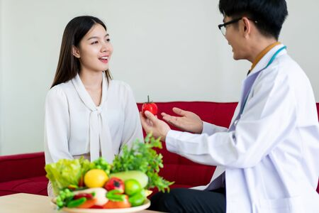 Beautiful young Asian woman come to meet the nutritionist in hospital and talking about dieting and health eating. Doctor explaining about healthcare to patient. Wellbeing and health eating concept. Foto de archivo