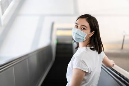 Woman wearing a hygiene protective mask to protect COVID19 virus and pm2.5 pollution while traveling in the crowded place. Woman use face mask to protect corona virus crisis in Asian country. Sickness