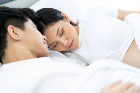 Lovely husband and wife sleeping together on the bed in bedroom close up. Husband embracing his pregnant wife with affectionate love. Closeness of Asian couple ethnicity portrait. Copy space available