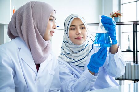 Asian young Muslim scientist testing the chemical experiment in hospital laboratory. Professional scientific pharmaceutical chemist investigating and making experiment in laboratory.