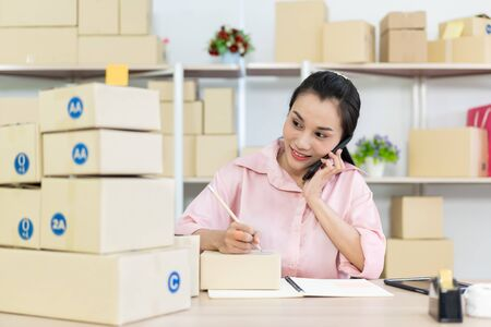 Beautiful young Asian woman online seller packing and checking for incoming orders in the warehouse. Young woman merchant selling products through online marketplace concept. 免版税图像