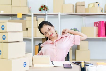 Online merchandise seller packing and preparing a packages in her workplace for shipment to customers. Woman relaxing and stretching herself after working for a longtime. ecommence merchandise concept