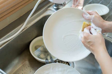 Used dirty dishwasher sponge left on the sink close up. Hygiene and healthcare in everyday lifestyle concept. 免版税图像