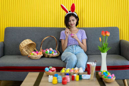 Asian young pretty woman enjoy taking a photo to the colorful fantasy Easter egg by using smartphone. Colorful fancy Easter egg in bucket. The symbolic of Easter egg festival concept.