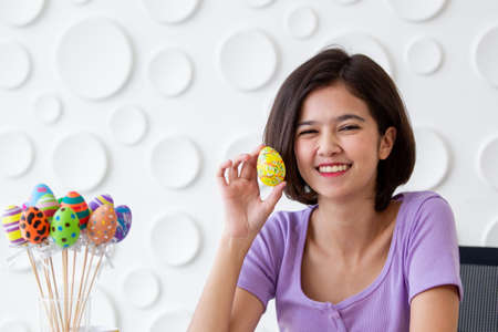 Asian young pretty woman enjoy painting a water colors on fantasy eggs for Easter egg festival. Beautiful colorful fancy Easter egg in bucket. The symbolic of Easter egg festival concept. 免版税图像