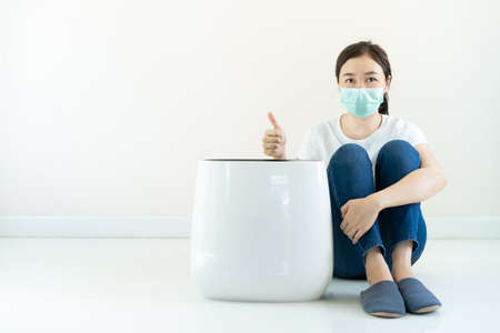 Beautiful Asian woman wearing a protective face mask sitting beside the modern portable air purifier and showing her thumb up close up with copy space. Wellbeing and good living lifestyle concept. 免版税图像