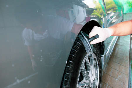 Asian worker in car care garage cleaning a dirty vehicle wheels by using brush and liquid soap foam close up with copyspace. Skilled Asian labor working in car care service concept.