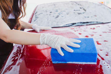 Cheerful beautiful Asian woman washing her modern red car by using a high pressurized water and car wash sponge. Young woman looking at the camera while she washing a car in garage with copyspace.